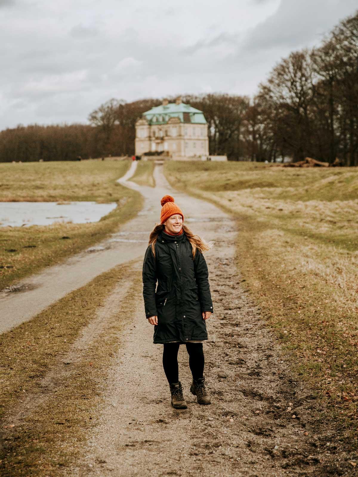 Sarah står på en af parforcejagtvejene med Eremitageslotet i baggrunden.