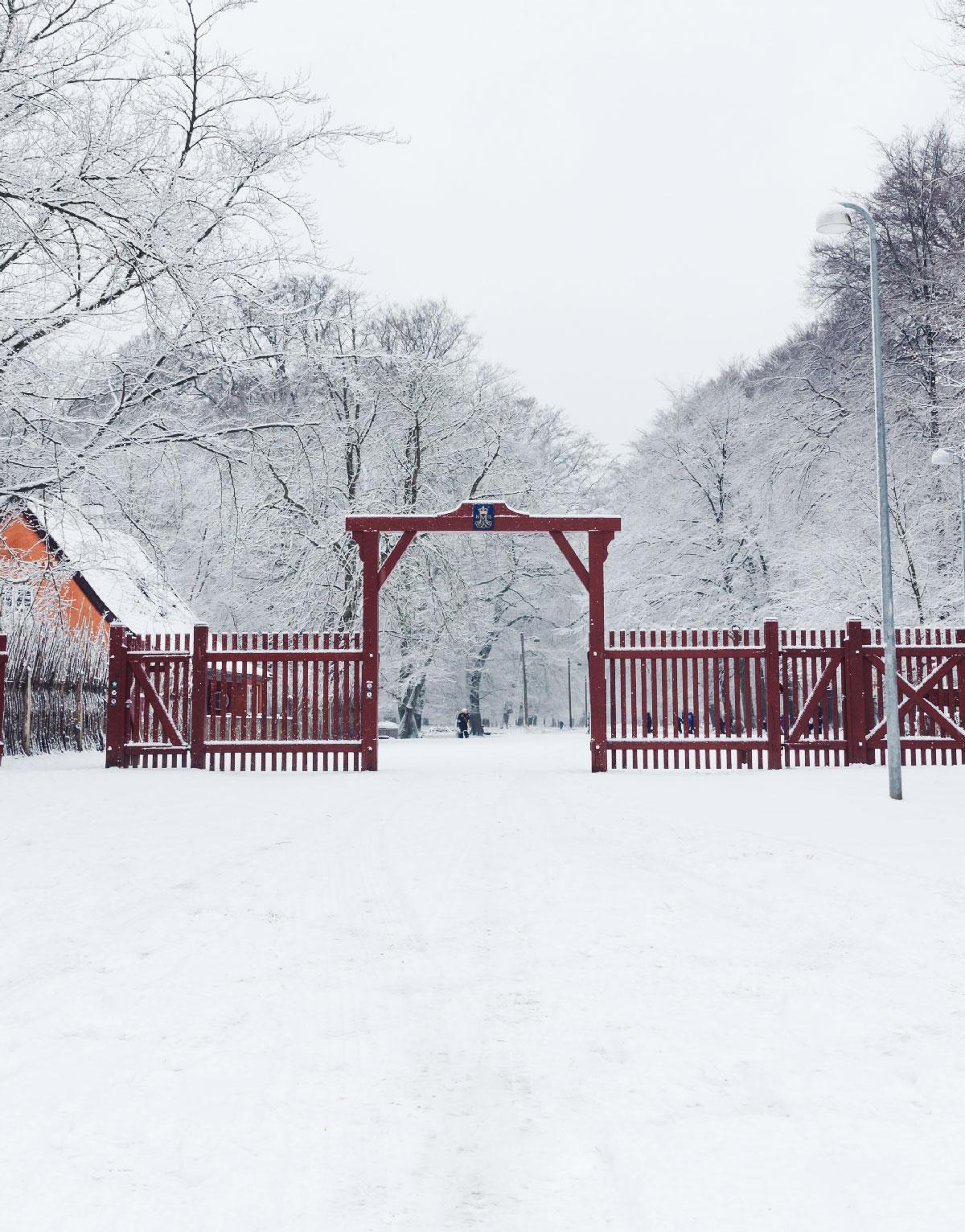En af de karakteristiske røde porte, som fører ind til Jægersborg Dyrehave. Porten og det øvrige landskab er sneklædt.